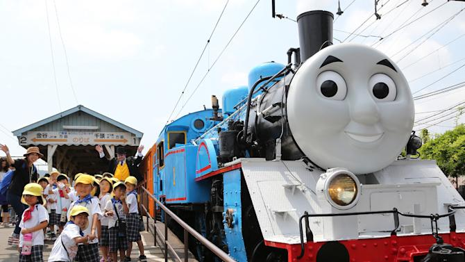 This picture taken on July 2, 2014 shows a life-sized Thomas the Tank Engine, surrounded by young schoolchildren at Shinkanaya station along Japan's Oigawa railway, in the city of Shimada in Shizuoka prefecture, west of Tokyo