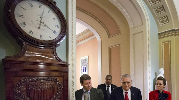 Senate Minority Whip Jon Kyl, center, from Arizona, walks to his office past the Ohio Clock, as the Senate works to avoid the fiscal cliff, on Capitol Hill on Monday, Dec. 31, 2012 in Washington. (AP Photo/Alex Brandon)