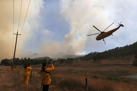Members of the media photograph a firefighting helicopter along Highway 20 during the Rocky Fire near Lower Lake, California