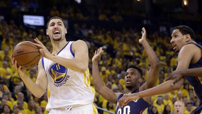 Golden State Warriors' Klay Thompson (11) drives to the basket as New Orleans Pelicans' Norris Cole (30) and Alexis Ajinca, right, defend during the first half in Game 1 of the NBA basketball playoffs Saturday, April 18, 2015, in Oakland, Calif. (AP Photo/Marcio Jose Sanchez)