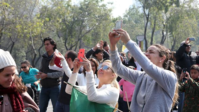 Residents of an upscale neighborhood take photographs of a helicopter carrying Pope Francis to Ecatepec where he will celebrate Mass before a crowd of hundreds of thousands, in Mexico City