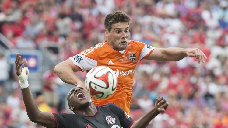 Toronto FC's Doneil Henry, left, gets tangled up with Houston Dynamos David Horst, center, and Warren Creavalle while battling for the ball during an MLS soccer match in Toronto on Saturday, July 12, 2014. (AP Photo/The Canadian Press, Darren Calabrese)