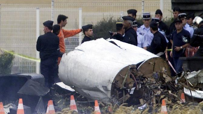 FILE - In this July 25, 2000, file photo, rescue workers stand on the crash site of an Air France Concorde plane that crashed in Gonesse, outside Paris, shortly after take off. A French appeals court is expected to decide on Thursday, Nov. 29, 2012, whether to uphold a manslaughter conviction against Continental Airlines for the crash over a decade ago of an Air France Concorde that killed 113 people. Continental Airlines, Inc. and one of its mechanics were convicted in 2010. (AP Photo/Michel Euler, File)