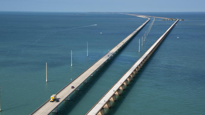 This aerial photo provided by the Florida Keys News Bureau shows the historic Seven Mile Bridge, right, in the Florida Keys near Marathon, Fla., Wednesday, March 19, 2014. The Monroe County Commission Wednesday ratified an agreement between the Florida Department of Transportation, the City of Marathon and the county to begin a 30-year, $77 million restoration and maintenance program on a 2.2-mile segment of the century-old span between Marathon and Pigeon Key. The bridge that once supported Henry Flagler's Florida Keys OverSea Railroad was retired in 1982, after the new span, left, opened to traffic. (AP Photo/Florida Keys News Bureau, Andy Newman)