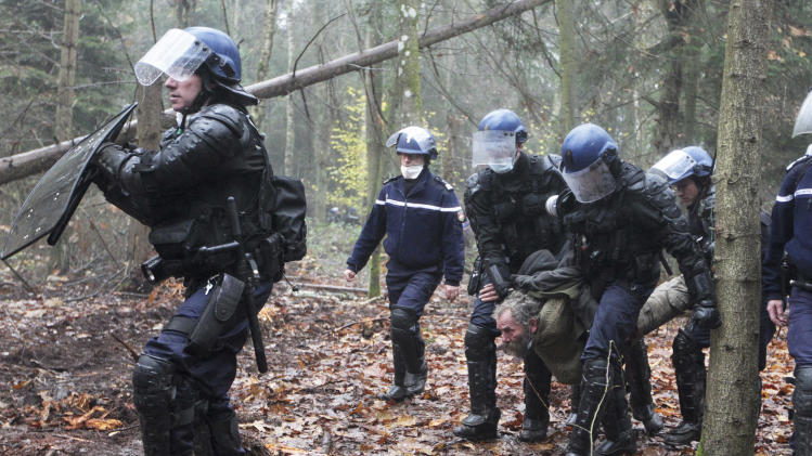 FILE - This Nov. 24, 2012 file photo shows French gendarmes detaining a protester during an evacuation operation on land that will become the new airport in Notre-Dame-des-Landes, western France. An unlikely alliance of anarchists and beret-wearing farmers is creating a headache for President Francois Hollande's beleaguered government by mounting an escalating Occupy Wall Street-style battle that has delayed construction on the ambitious airport near the city of Nantes for months. (AP Photo/Laetitia Notarianni, File)