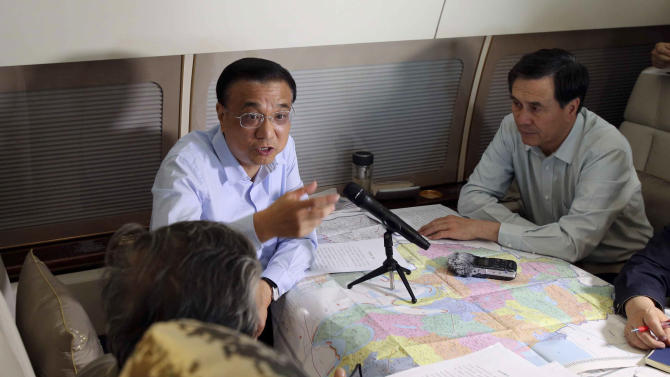 In this photo released by China's Xinhua News Agency, Chinese Premier Li Keqiang, center, chairs a meeting to direct search and rescue work as he takes a plane to the site where a passenger ship sank in the Yangtze River in central China's Hubei Province, Tuesday, June 2, 2015. A small cruise ship sank overnight in China's Yangtze River during a storm, leaving nearly 450 people missing, most of them elderly, state media said Tuesday. (Ding Lin/Xinhua via AP) NO SALES
