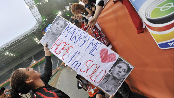 United States goalkeeper Hope Solo holds a fan's sign after the US won 3-1 the semifinal match between France and the United States at the Women's Soccer World Cup in Moenchengladbach, Germany, Wednesday, July 13, 2011. (AP Photo/Martin Meissner)