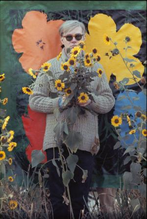 """In this 1964 photo provided by Allen Cooper Enterprises, artist Andy Warhol stands in a field of Black-Eyed Susans in New York. The image will be featured in an exhibit entitled: """"Before They Were Famous: Behind the Lens of William John Kennedy,"""" which opens on April 19th at the Site/109 gallery in New York. (AP Photo/William John Kennedy via Allen Cooper Enterprises)"""
