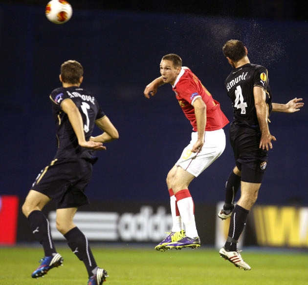 Dinamo's Jozo Simunovic, left, and Dinamo's Josip Simunic jump for a ball with PSV's Tim Matavz during a Europa League group B soccer match between PSV Eindhoven and Dinamo Zagreb, in Zagreb, Croatia,
