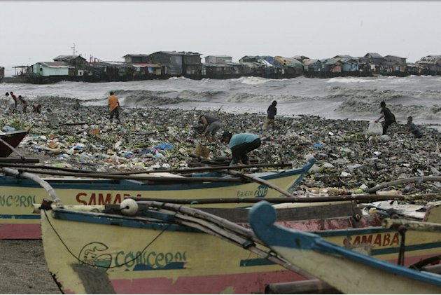 Small outriggers use by fishermen are secured on the shore as people gather salvagable materials from the debris brought by Typhoon Nanmadol Saturday, Aug. 27, 2011 in Manila, Philippines. Forecasters