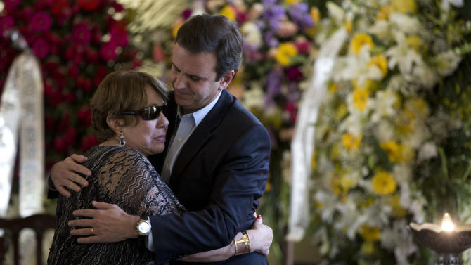 "Vera Lucia, wife of Brazilian architect Oscar Niemeyer, left, embraces Rio de Janeiro's Mayor Eduardo Paes next to the coffin containing the remains of Niemeyer, at the ""Palacio da Cidade"" or ""City Palace"", in Rio de Janeiro, Friday, Dec. 7, 2012. Niemeyer, 104, the groundbreaking architect who designed Brazil's futuristic capital and much of the United Nations complex, died Wednesday night in Rio de Janeiro, the seaside city where he was born and where his remains will be buried. (AP Photo/Felipe Dana)"
