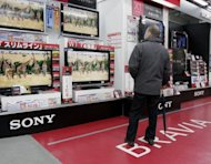 A customer looks at Sony Bravia LCD TVs at an electronics shop in Tokyo, 2009. Sony reported a widening quarterly loss and trimmed its profit forecast for the year, again underscoring the challenges faced by Japan's troubled electronics giants