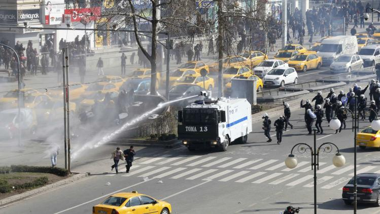 Riot police fires a water cannon to disperse anti-government demonstrators gathered to mark the funeral of Berkin Elvan in Ankara
