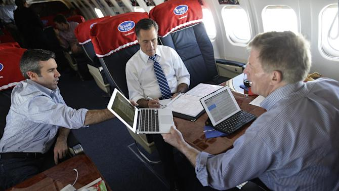 Republican presidential candidate and former Massachusetts Gov. Mitt Romney, center, collaborates with senior adviser Kevin Madden, left, and chief strategist Stuart Stevens, right, during a strategy meeting on their campaign plane en route to Dayton International Airport in Vandalia, Ohio, Sunday, Oct. 28, 2012. (AP Photo/Charles Dharapak)