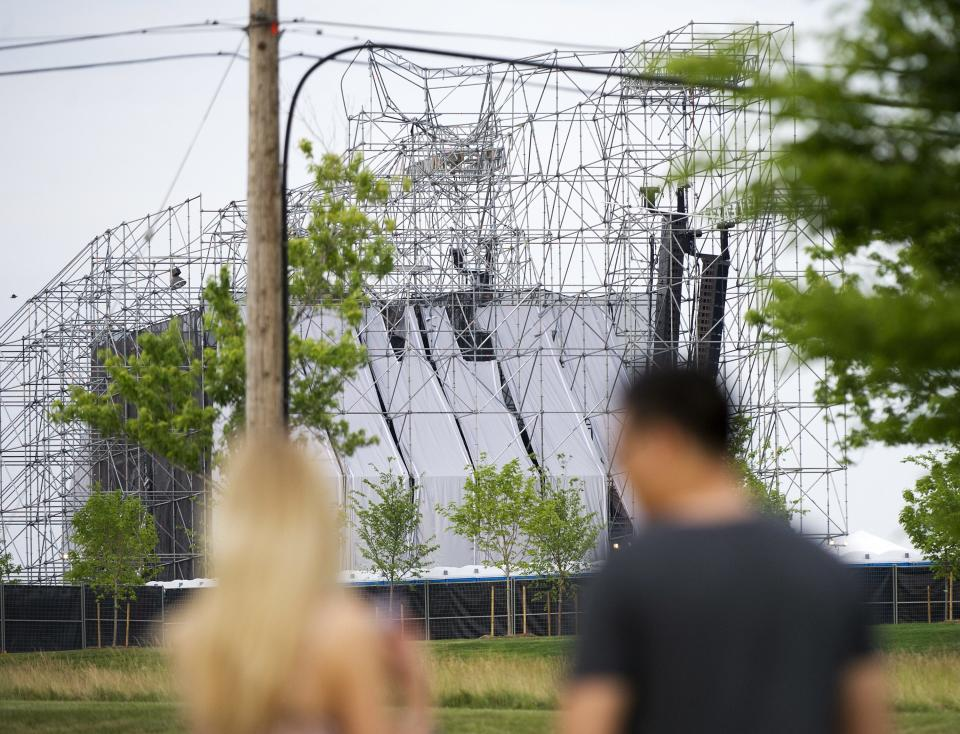 People look at a collapsed stage at Downsview Park in Toronto on Saturday, June 16, 2012.  Toronto paramedics say one person is dead and another is seriously hurt after the stage collapsed while setting up for a Radiohead concert. They say two other people were injured and are being assessed. (AP Photo/The Canadian Press, Nathan Denette)