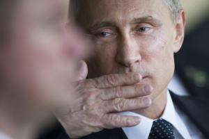 Russia's President Vladimir Putin motions to blow…
