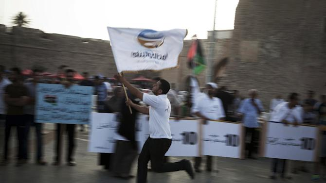 A Libyan Muslim Brotherhood supporter runs holding a flag of the party in Martyr's Square in Tripoli, Libya, Thursday, July 5, 2012. The Libyan National Assembly elections will take place on July 7, 2012, the first free elections since 1969. (AP Photo/Manu Brabo)