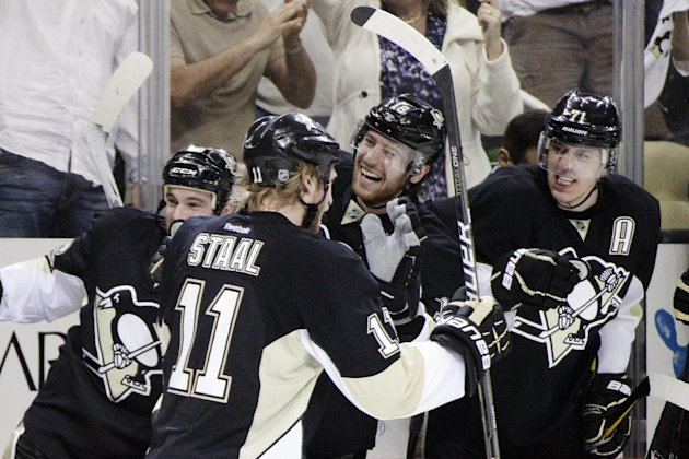 Pittsburgh Penguins' Jordan Staal (11) celebrates his second-period goal with Steve Sullivan, left, James Neal (18) and Evgeni Malkin (71) during Game 5 of an opening-round NHL Stanley Cup hockey playoff series against the Philadelphia Flyers in Pittsburgh Friday, April 20, 2012. (AP Photo/Gene J. Puskar)