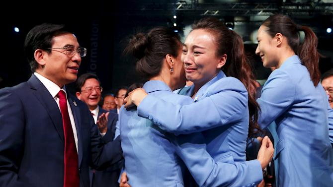 Members of the Beijing delegation hug after Beijing was awarded the 2022 Winter Olympic Games, defeating Almaty in the final round of voting, during the 128th IOC session in Kuala Lumpur