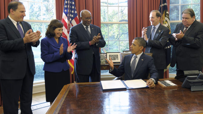 President Barack Obama speaks in the Oval Office of the White House in Washington, Friday, Oct. 21, 2011, where he signed the renewal of the Trade Adjustment Assistance for workers. From left are, Deputy Labor Secretary Seth Harris, Labor Secretary Hilda Solis, US Trade Representative Ron Kirk, Rep. Dave Camp, R-Mich., and United Steelworkers Vice President Thomas Conway. (AP Photo/Susan Walsh)