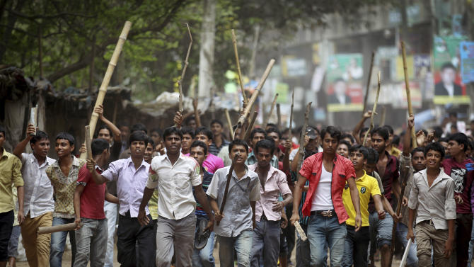 """Protestors march down a street demanding the death penalty for those responsible for the collapsed garment factory building, killing hundreds, Tuesday, April 30, 2013 in Savar, near Dhaka, Bangladesh.  A top Bangladesh court on Tuesday ordered the government to """"immediately"""" confiscate the property of a collapsed building's owner, as thousands of protesters demanding death penalty for the man clashed with police, leaving 100 people injured. (AP Photo/Wong Maye-E)"""
