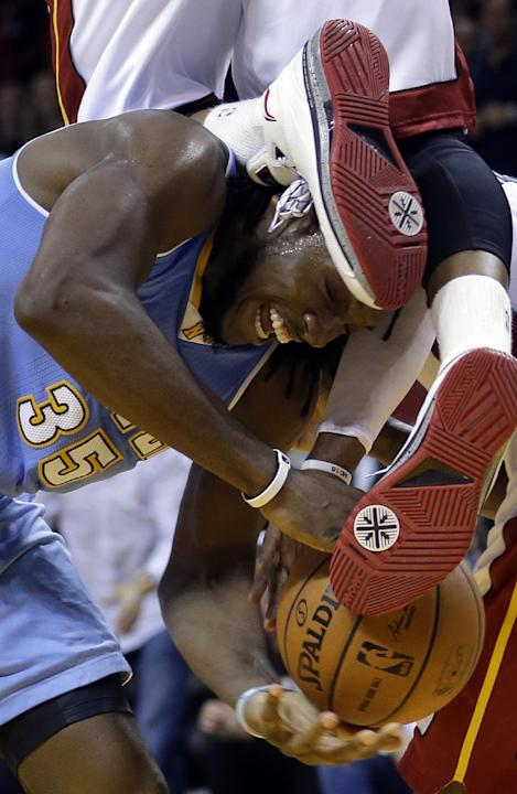 Denver Nuggets forward Kenneth Faried (35) is fouled by Miami Heat guard Dwyane Wade, top, during the second half of an NBA basketball game in Miami, Friday, March 14, 2014. The Nuggets won 111-107