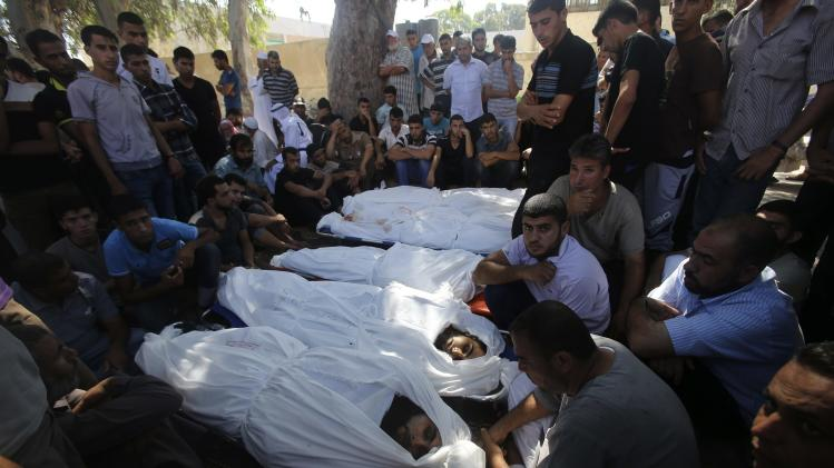 People gather around the bodies of Palestinians from al-Astal family, whom medics said were killed in an Israeli air strike on their house, during their funeral in Khan Younis
