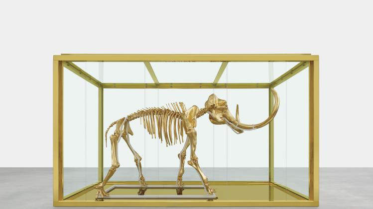 "In this 2014 photo released by Damien Hirst and Science Ltd., British artist Damien Hirst's latest piece entitled ""Gone but Not Forgotten"", which features the gilded skeleton of a woolly mammoth in a steel and glass vitrine, is displayed. Famed British artist Damien Hirst has created a gilded woolly mammoth skeleton encased in a gold tank to be auctioned off at the annual amfAR Cinema Against AIDS gala in Cap d'Antibes, southern France, on Thursday, May 22, 2014. (AP Photo/Prudence Cuming Associates via Damien Hirst)"