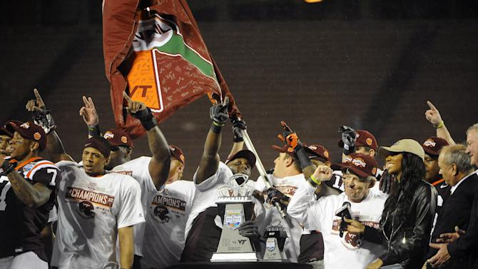 Virginia Tech players take the stage with their trophy after defeating  Rutgers 13-10 in overtime of an NCAA college football Russell Athletic Bowl game on Friday, Dec. 28, 2012, in Orlando, Fla. (AP Photo/Brian Blanco)