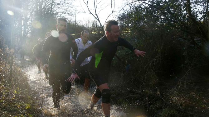 Prime Minister Cameron reacts as he competes in the Great Brook Run, a mile long course through water and mud, at Chadlington in southern England