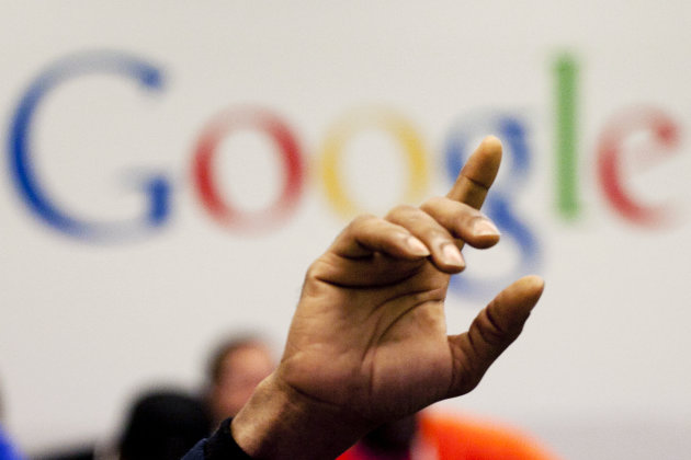 FILE - In this Oct. 17, 2012, file photo, a man raises his hand during at Google offices. Google's stock price topped $800 for the first time Tuesday, Feb. 20, 2013, amid renewed confidence in the com