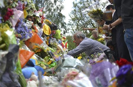 Mourners place flowers outside the home of the late South African President Nelson Mandela in Houghton, Johannesburg