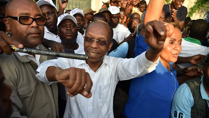 Former Haitian President Jean Bertrand Aristide (C) greets supporters at the entrance of his home in Port-au-Prince, on September 30, 2015, after giving a speech for the opening ceremony of the Lavalas Political Party