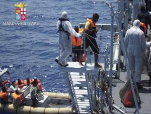 Handout picture of migrants walking aboard the Italian navy ship Scirocco during a rescue operation about 40 nautical miles off the coast of Libya