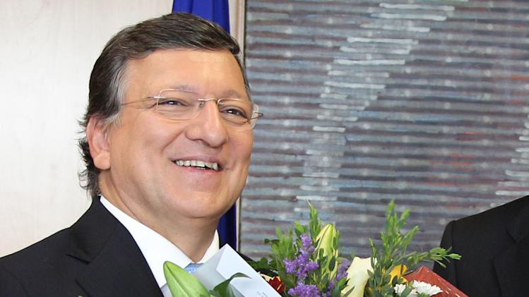 European Commission President Jose Manuel Barroso reacts, as he received flowers by Norway's ambassador to the EU Atle Leikvoll, after the 2012 Nobel Peace Prize was given to the EU, at the European Commission headquarters in Brussels, Friday, Oct. 12, 2012. The European Union won the Nobel Peace Prize on Friday for its efforts to promote peace and democracy in Europe, an award given even though the bloc is struggling with its biggest crisis since it was created in the 1950s.  (AP Photo/Yves Logghe)