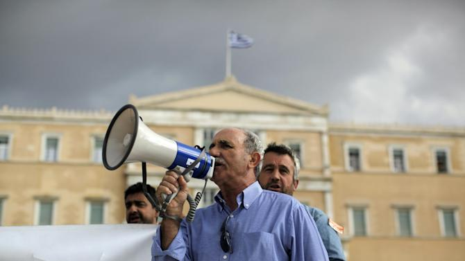 A municipal worker shout slogans during a protest against budget cuts in front of the Greek Parliament in Athens. Saturday Nov. 10 2012.  Greece's Parliament last week passed hugely unpopular new cutbacks demanded by the country's bailout creditors in exchange for more rescue loans. But Athens is not expected to get the money next week, as it had initially hoped, because European officials need time to study a report on Greece's public finances. (AP Photo/Kostas Tsironis)