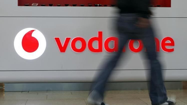 A customer walks past the Vodafone logo in a shopping mall in Prague