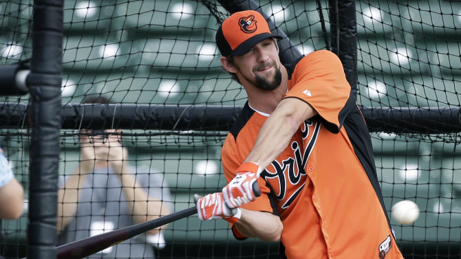 Former Olympic swimmer Michael Phelps hits in the batting cage during a Baltimore Orioles baseball spring training workout Thursday, Feb. 21, 2013, in Sarasota, Fla.  Phelps, a native of Baltimore who was in the area filming his Golf Channel show The Haney Project, took batting practice with the team. (AP Photo/Charlie Neibergall)