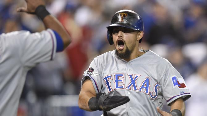 Texas Rangers' Rougned Odor, right, celebrates after scoring during the 14th inning of baseball Game 2 of the American League Division Series against the Toronto Blue Jays in Toronto, Friday, Oct. 9, 2015. (Frank Gunn/The Canadian Press via AP) MANDATORY CREDIT