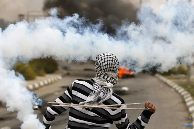 A Palestinian stone-thrower uses a sling to throw back a tear gas canister fired by Israeli security forces during clashes near Ramallah