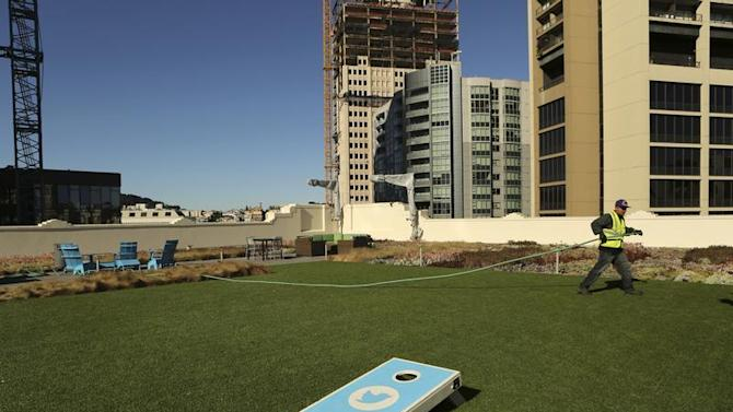 A worker tends to the lawn on the roof of Twitter headquarters in San Francisco