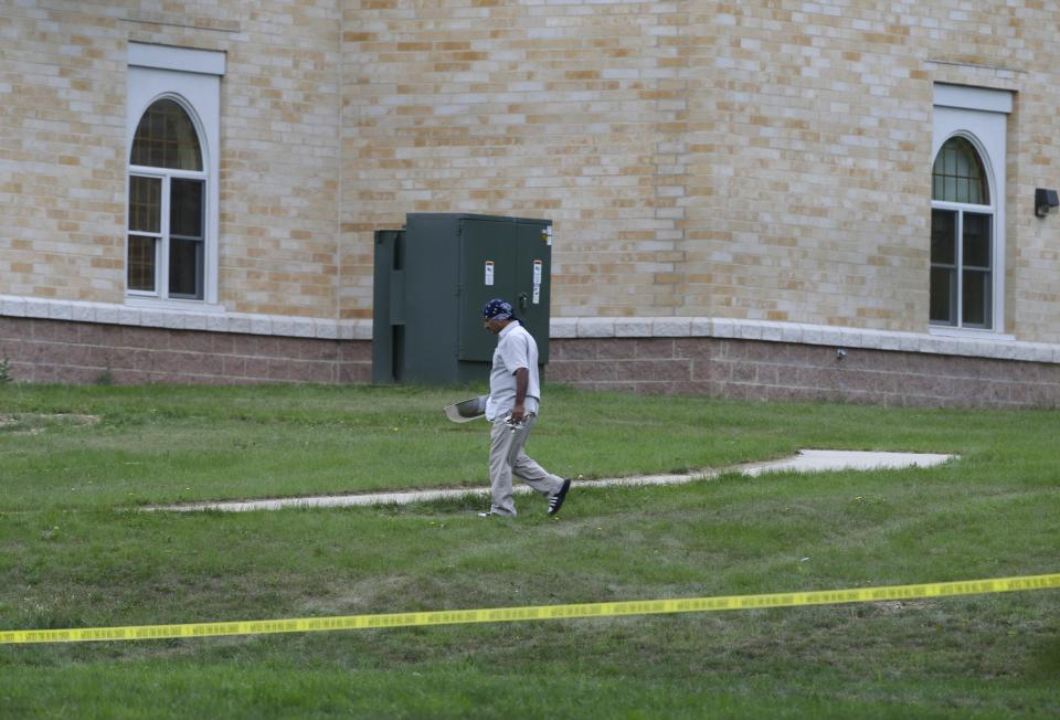 A member of the Sikh temple of Wisconsin walks with an item as people return for the first time in Oak Creek, Wis. Thursday, Aug 9, 2012.  The mass shooting last Sunday claimed six members of the temple. (AP Photo/Jeffrey Phelps)