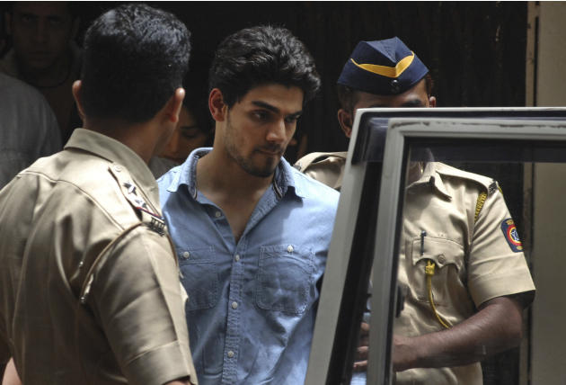 Suraj Pancholi, the son of Bollywood couple Aditya Pancholi and Zarina Wahab is escorted by police as he leaves after appearing before a court in Mumbai, India, Tuesday, June 11, 2013. Pancholi, has b