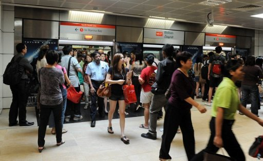 This file photo shows commuters on an SMRT train arriving at Bishan train station interchange in Singapore, in April. Singapore&#39;s first strike in 26 years petered out with most of the Chinese bus drivers who had stopped working to demand higher pay reporting for duty