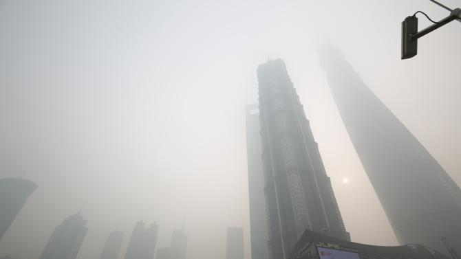 An electronic screen and buildings are seen amid heavy smog at the financial district of Pudong in Shanghai