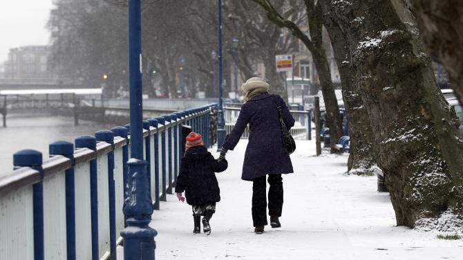 People walk along a snow covered  embankment at Putney Bridge,  in London, Sunday, Jan. 20, 2013. The big freeze across the UK is here to stay, with more snow expected next week. (AP Photo/Sang Tan)