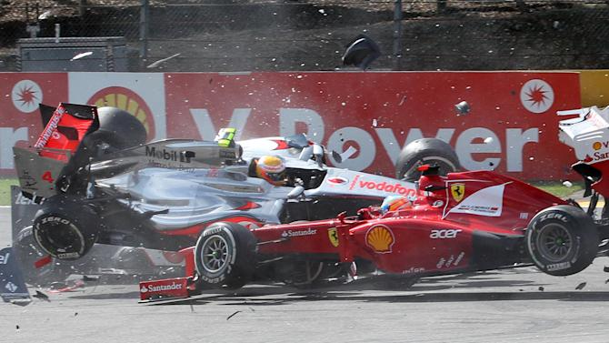 McLaren Mercedes driver Lewis Hamilton of Britain, yellow helmet left, crashes with Ferrari driver Fernando Alonso of Spain, right, during the first lap of the Belgian Formula One Grand Prix in Spa-Francorchamps, Sunday, Sept. 2, 2012.  (AP Photo/Luca Bruno)