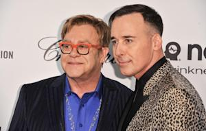 Elton John, left, and David Furnish arrive at the 2014 …