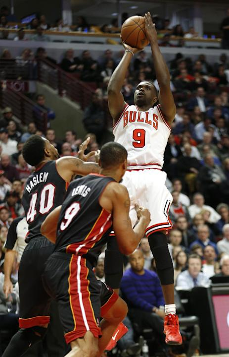 Chicago Bulls forward Luol Deng (9) shoots over Miami Heat forward Udonis Haslem (40) and forward Rashard Lewis (9) during the second half of an NBA basketball game in Chicago, Thursday, Dec. 5, 2013.