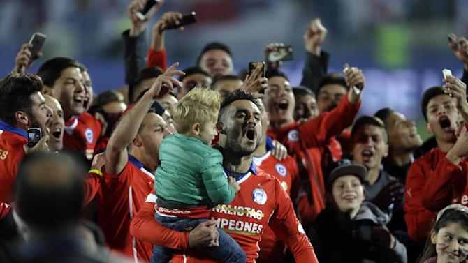 Players celebrate at the stadium at the end of  the Copa America final soccer match between Argentina and Chile at the National Stadium in Santiago, Chile, Saturday, July 4, 2015. Goalkeeper Claudio Bravo made a save and striker Alexis Sanchez converted the winning penalty as host Chile defeated Argentina 4-1 in a shootout after a 0-0 draw in the Copa America final, finally winning its first major title.(AP Photo/Natacha Pisarenko)